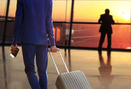 travellers: Business man with suitcase in hall of airport