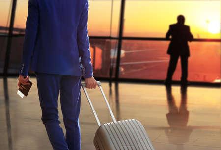 pasaporte: Hombre de negocios con la maleta en el pasillo del aeropuerto Foto de archivo