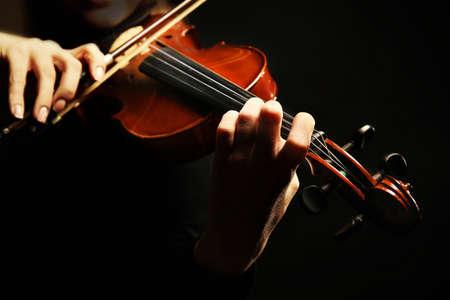Violiste viool te spelen op donkere achtergrond
