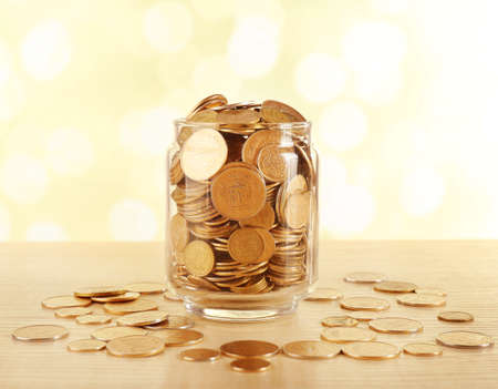 gold coins: Gold coins in glass bottle on bright blurred background Stock Photo