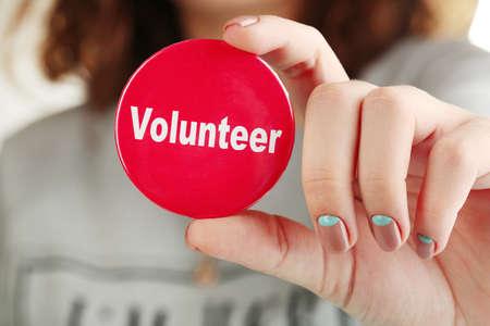 Round volunteer button in hand close-up Reklamní fotografie