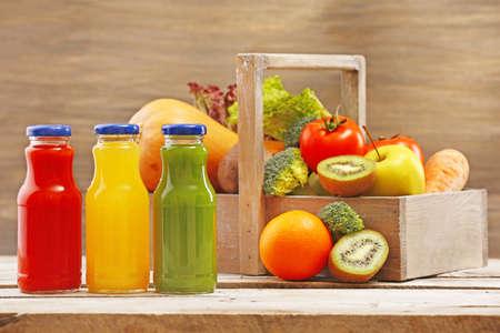 jugos: Las botellas de vidrio de jugo fresco y saludable con el conjunto de frutas y verduras en el fondo de madera