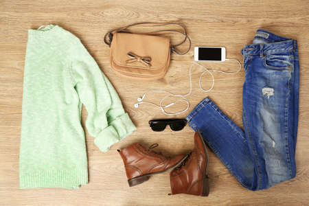 composed: Still life of casual woman. Woman clothes and accessories on wooden background