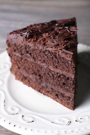 rebanada de pastel: delicioso pastel de chocolate en plato blanco sobre fondo de madera, de cerca Foto de archivo
