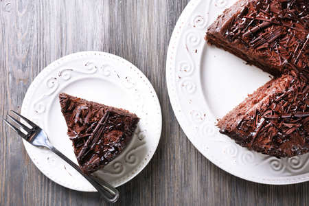 Sliced tasty chocolate cake on wooden table