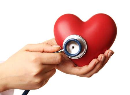 enfermedades del corazon: Médico manos con el corazón y el estetoscopio aislados en blanco