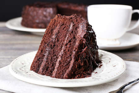 Delicious chocolate cake in white plate on wooden table , closeup 스톡 콘텐츠