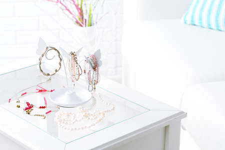 Decorative stand with jewelry and bijouterie on table in room Imagens