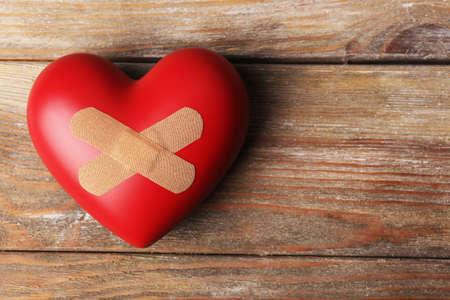 planks: Heart with plaster on wooden planks background Stock Photo