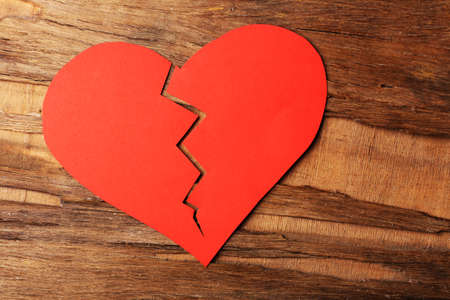 Broken heart on rustic wooden table background