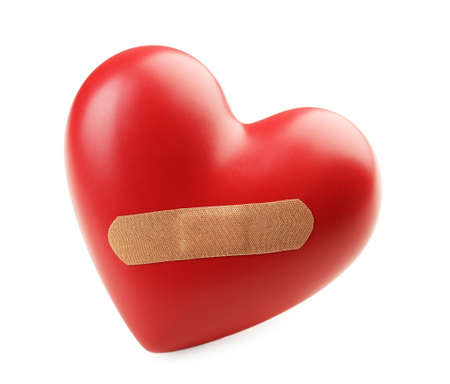 mended: Red heart with plaster isolated on white