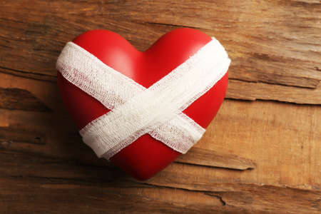 mended: Tied heart with bandage on rustic wooden table background Stock Photo