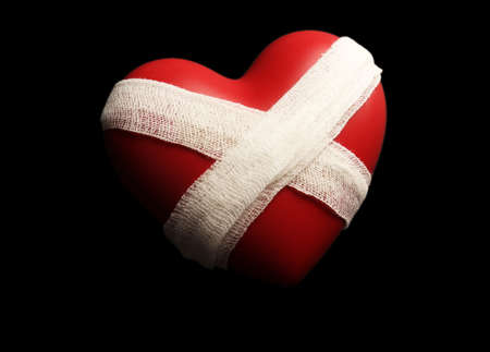 mended: Tied heart with bandage on black background Stock Photo