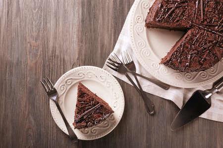 rebanada de pastel: Delicioso pastel de chocolate rebanada con los cubiertos en la mesa de madera