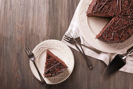 Sliced delicious chocolate cake with cutlery on wooden table