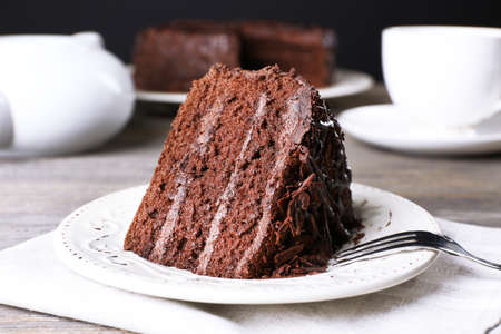 CAKE: delicioso pastel de chocolate en plato blanco sobre la mesa de madera, de cerca