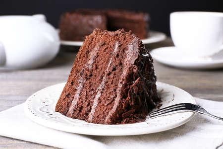 Köstlicher Schokoladenkuchen in der weißen Platte auf Holztisch, Nahaufnahme Standard-Bild