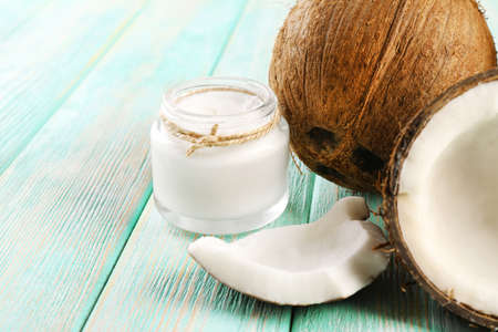 aceite de coco: El aceite de coco fresco en la cristaler�a en el color de fondo de la tabla de madera Foto de archivo