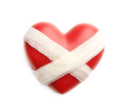 heart pain: Tied heart with bandage isolated on white Stock Photo