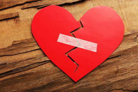 mended: Broken heart with plaster on rustic wooden table