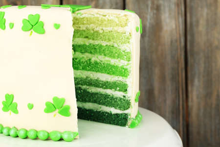 three leafed: Sliced cake for Saint Patricks Day on stand and wooden