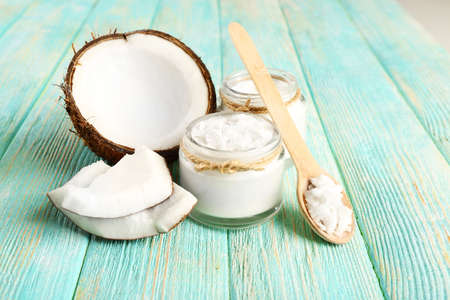 Fresh coconut oil in glassware and wooden spoon on color wooden table background Stock Photo