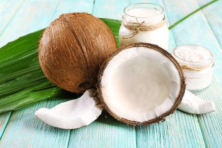 Verse kokosnoot olie in glaswerk en groen blad op kleur houten tafel achtergrond