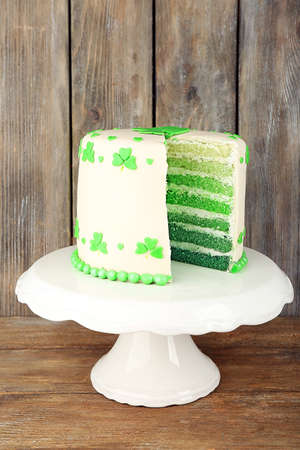 three leafed: Sliced cake for Saint Patricks Day on stand and wooden background