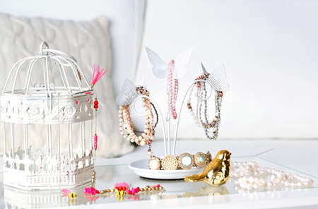 Decorative stand with jewelry and bijouterie on table in room Stock Photo