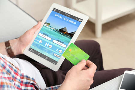 Man holding tablet with screen interface of booking hotels Reklamní fotografie - 43314108