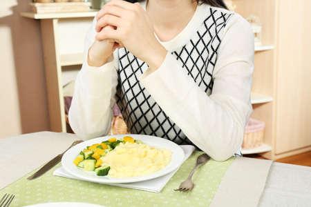 eating dinner: Woman praying before eating