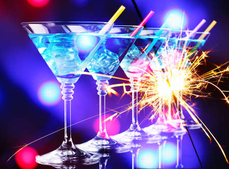 Blue cocktail in martini glasses on bright background