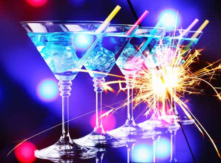 celebra: Cóctel azul en copas de martini en fondo brillante
