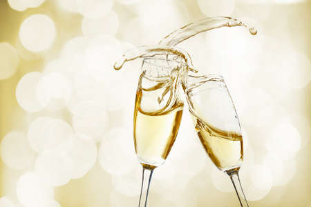 Glasses of champagne with splash on bright background