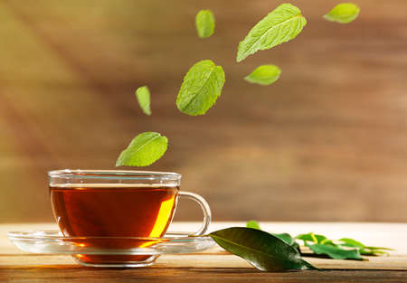 Mint leaves falling in cup of green tea on wooden background
