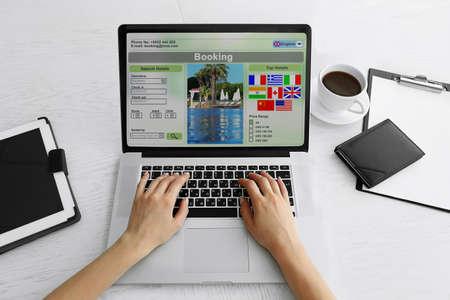 orden de compra: Mujer que usa la computadora port�til de reserva de hoteles en linea Foto de archivo