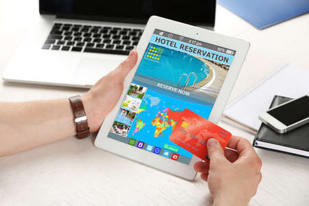 concept hotel: Man holding tablet with screen interface of booking hotels