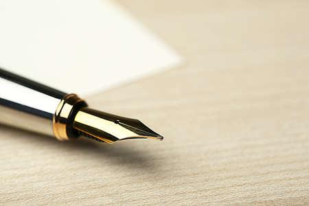 Plnicí pero na bílém listu papíru a dřevěný stůl pozadí