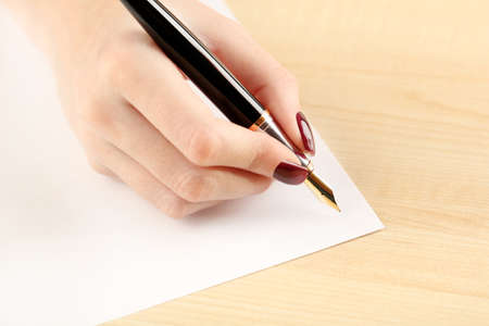 letter writing: Female hand writing letter on white sheet of paper by fountain pen on wooden table background Stock Photo