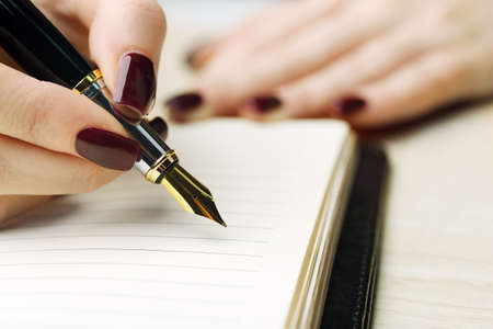 business letter: Female hand writing in diary by pen on wooden table background Stock Photo