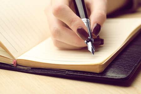 木製のテーブル背景にペンで日記に書く女性の手