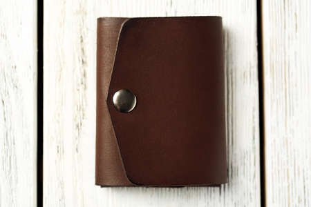 Hand made leather man wallet on white wooden background Stock Photo