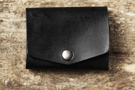 Hand made leather man wallet on wooden background Stock Photo