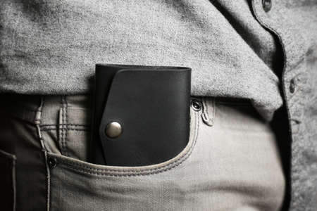 Man hand made leather wallet in pocket, close up