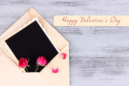 old envelope: Old envelope with blank photo paper and beautiful pink dried roses on wooden background