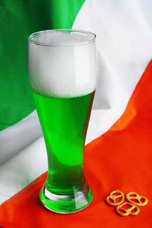 alehouse: Glass of green beer on Ireland flag background