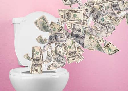 A lot of money is flushed down the toilet. Foto de archivo