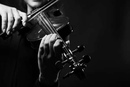 woman violin: Violinist playing violin on dark background