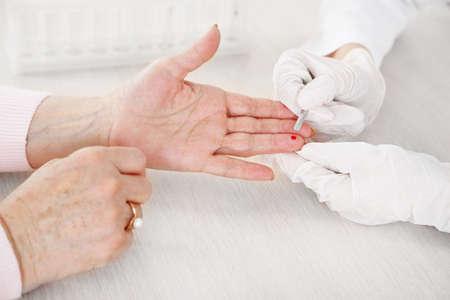 control de calidad: Enfermera con la jeringuilla está tomando la sangre para la prueba en el hospital