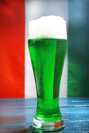 beerhouse: Glass of green beer on Ireland flag background